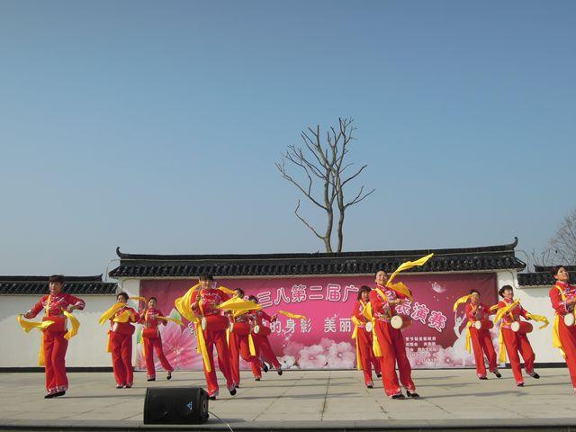 """为扶持基层文化建设,鼓励群众积极参与文化活动。3月11日上午,誓节镇妇联联合镇文化站、镇共青团及镇工会在茆林村文化广场举办了""""舞动的身影,美丽的风景""""——庆三八第二届广场舞表演赛。 茆林村腰鼓队的《开门红》为本届广场舞表演赛拉开了序幕,来自誓节镇各村(社区)的九支代表队参加了本次比赛。比赛现场,广场舞爱好者们用优美的舞姿展现了良好的精神面貌和竞技水平,充分展示了新时代农村女性的风采,同时也为现场观众带来了一场精彩的视觉盛宴。来自东冲村的广场舞爱好者们用一"""